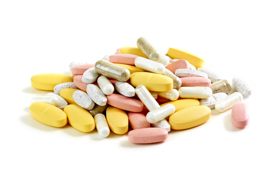 Mix of vitamins and herbal supplements on white background